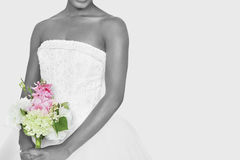 Midsection of bride holding bouquet over gray background Stock Photos