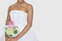 Midsection of bride holding bouquet over gray background Royalty Free Stock Images