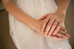 Midsection of bride wearing wedding ring while sitting on sofa Stock Photos