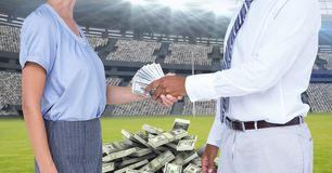 Midsection of business people exchanging money at football stadium representing corruption royalty free stock photo
