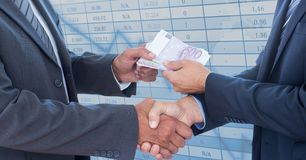 Midsection of business people shaking hands while holding money representing corruption concept Royalty Free Stock Image
