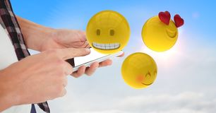 Midsection of business person using smart phone while emojis flying in sky. Digital composite of Midsection of business person using smart phone while emojis Royalty Free Stock Photography