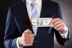 Midsection of businessman burning money. Against black background stock images