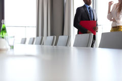 Midsection of businessman and businesswoman standing by conference table in office Stock Photography