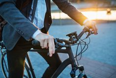 Midsection of businessman commuter with electric bicycle traveling from work in city. Midsection of businessman commuter with electric bicycle traveling home stock photos
