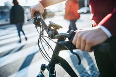A midsection of businessman commuter with electric bicycle traveling to work in city. A close-up royalty free stock photos