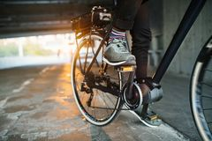 Midsection of businessman commuter with electric bicycle traveling from work in city. Midsection of unrecognizable businessman commuter with electric bicycle royalty free stock images