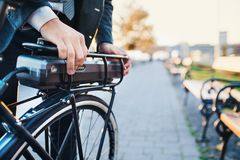 A midsection of businessman commuter setting up electric bicycle in city. A midsection of businessman commuter setting up electric bicycle when traveling home royalty free stock image