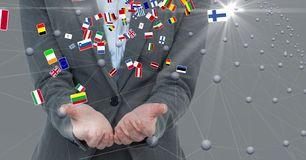 Midsection of businessman with cupped hands and various flags Royalty Free Stock Photo