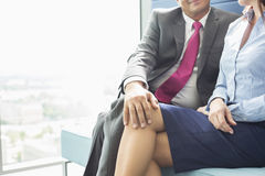 Midsection of businessman flirting with female colleague in office Royalty Free Stock Images