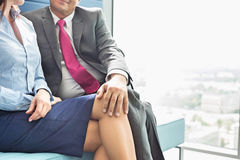 Midsection of businessman flirting with female colleague in office Royalty Free Stock Photography