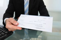 Midsection of businessman giving cheque Royalty Free Stock Photography