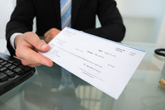 Midsection Of Businessman Giving Cheque Royalty Free Stock Image
