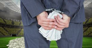 Midsection of businessman with handcuffs and money at football stadium representing corruption Royalty Free Stock Photography