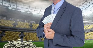 Midsection of businessman hiding money at soccer stadium representing corruption concept. Digital composite of Midsection of businessman hiding money at soccer Royalty Free Stock Photo