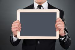 Midsection of businessman holding blank slate Stock Image