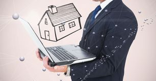 Midsection of businessman holding laptop with house drawn in background stock photos