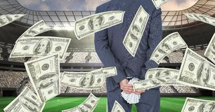 Midsection of businessman holding money behind back at football stadium representing corruption Stock Photo