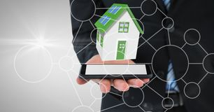 Midsection of businessman with house on device. Digital composite of Midsection of businessman with house on device Stock Photo
