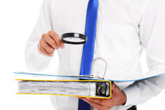 Midsection of a businessman searching documents with magnifying Stock Photography