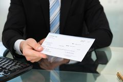 Midsection of businessman showing cheque Stock Image
