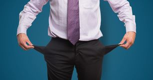 Midsection of businessman showing empty pockets against blue background. Digital composite of Midsection of businessman showing empty pockets against blue Stock Images
