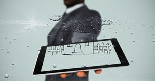 Midsection of businessman showing house on tablet PC`s screen. Digital composite of Midsection of businessman showing house on tablet PC`s screen Stock Image