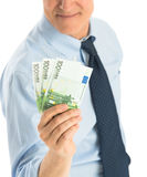 Midsection Of Businessman Showing One Hundred Euro Banknotes. Midsection of mature businessman showing euro banknotes while standing against white background Royalty Free Stock Photography