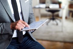 A midsection of businessman sitting in an office, using tablet. Copy space. royalty free stock image
