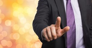 Midsection of businessman touching imaginary screen over bokeh Stock Photography