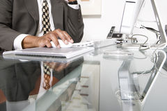 Midsection Of Businessman Using Computer. Midsection of a businessman using computer at office stock image