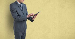 Midsection of businessman using digital tablet over colored background Royalty Free Stock Image