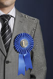Midsection Of Businessman Wearing Blue Ribbon On Lapel. Closeup midsection of a businessman wearing blue ribbon on lapel against dark background mid section Royalty Free Stock Images