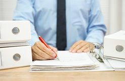 Midsection of businessman working with financial documents at d. Esk in the office royalty free stock photos