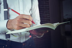 Midsection of businessman writing in his notepad Stock Images