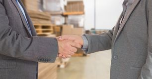 Midsection of businessmen doing handshake in warehouse Royalty Free Stock Photography