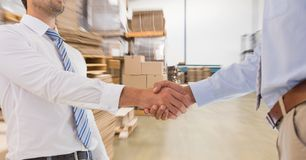 Midsection of businessmen doing handshake in warehouse Royalty Free Stock Images