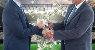 Midsection of businessmen exchanging money while shaking hands on soccer field representing corrupti. Digital composite of Midsection of businessmen exchanging royalty free stock photos