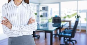Midsection of businesswoman with arms crossed standing against desk in office Royalty Free Stock Image