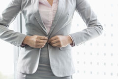 Midsection of businesswoman buttoning her blazer Stock Images
