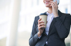 Midsection of businesswoman using cell phone while holding disposable cup outdoors Stock Image