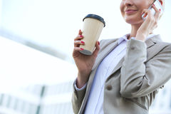 Midsection of businesswoman using cell phone while holding disposable cup outdoors Stock Photo