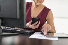 Midsection Of Businesswoman Using Technologies At Desk. Midsection of mature businesswoman using technologies at desk in office Stock Photography