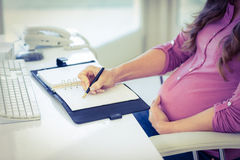 Midsection of businesswoman writing in diary Royalty Free Stock Images