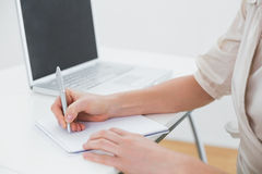 Midsection of a businesswoman writing notes by laptop Stock Image