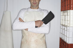 Midsection Of Butcher With Cleaver Arms Crossed Stock Photo