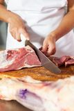 Midsection Of Butcher Slicing Fresh Raw Meat. Midsection of female butcher slicing fresh raw meat at counter in shop Royalty Free Stock Image