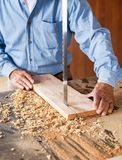 Midsection Of Carpenter Cutting Wood With Bandsaw Stock Photo