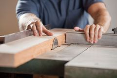 Midsection Of Carpenter Cutting Wood With Tablesaw Royalty Free Stock Images