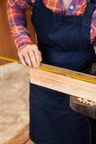 Midsection Of Carpenter Measuring Wood Royalty Free Stock Images